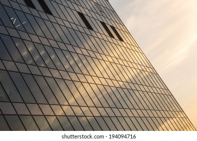 Glass facade of office building at sunset