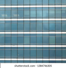 The glass facade of skyscraper with many identical windows. Same blue glasses structure of house wall.