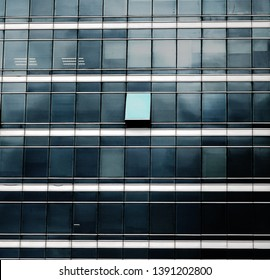The glass facade of skyscraper with many identical windows and only one window is different. Same glasses structure of house wall with one exception - open window.