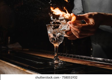 Glass of fiery cocktail on the bar counter against the background of bartender`s hands with fire
