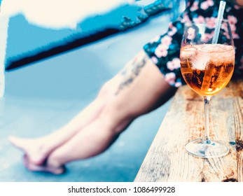 a glass filled up with Aperol Spritz. A cocktail on a bench. In the background, blurred, the legs of a woman.