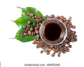 Glass filled with hot coffee, roasted beans and green leaves scattered around. White isolated background, captured from top view with sharp focus