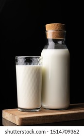 A glass filled with milk and a bottle with milk on a wooden board. Black background. Glass bottle. Natural cork. White drink. Cow's milk.