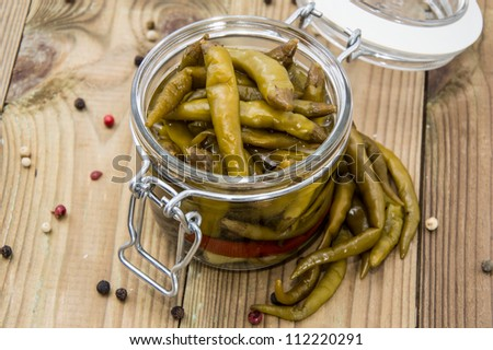 Glass filled with pickled Chilis on wooden background