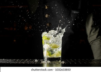 Glass filled with splashing fresh Caipirinha cocktail on the bar counter against the dark background of barman