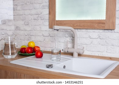 The glass is filled with tap water in the kitchen