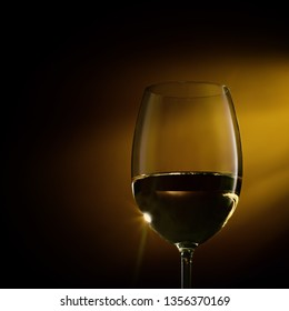 Glass filled with white wine on a gradient background. Close-up studio shot.