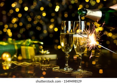 Glass is filling with champagne, sparkler is burning. New Year golden decor, balls, presents are on table. Festive decorative garland with yellow light bulbs are shining on background. Christmas mood.
