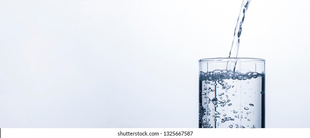 Glass is filling with a stream of clean and refreshing water on a white background. Concept of quenching thirst and cooling drinks in hot weather. Water balance and daily water consumption. Banner.