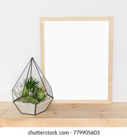 Glass florarium vase with succulent plants and wooden frame with place for text on wooden background. Small garden with miniature cactuse, echeveria, crassula. Home indoor plants. Mock up.