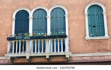 Glass flowers in red, white and blue on a balcony with blue doors on the island of Murano