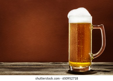A Glass Of Foaming Beer On A Wooden Table Isolated On Brown Background