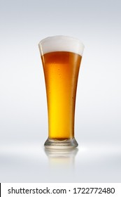 A glass of foamy beer on a glossy tabletop with bright gradient background