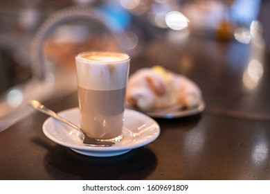 "A Glass with a Foamy Italian ""Caffelatte""and a blurred cream ""cornetto"" (Croissant) on the wooden counter of a bar in Rome"