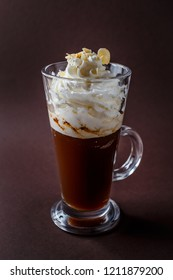 Glass of frappucino with whipped cream and almonds shaving on elegant dark brown background.