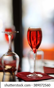 Glass with French alcohol drink Kir Royal on the table at the restaurant