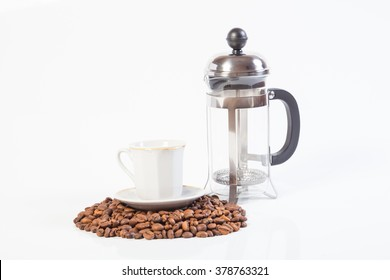Glass french press, coffee beans and cup isolated on white background