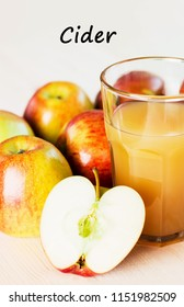 Glass of fresh apple cider and half apple near autumn apples. Wooden background, text cider.