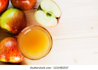 Glass of fresh apple juice and half apple near autumn apples. Wooden background, view from above, space for text.