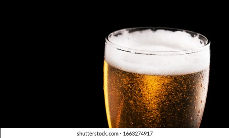 Glass of fresh beer isolated on a black background. Banner size. Wide format.