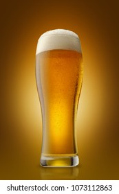 A glass of fresh beer on a yellow background