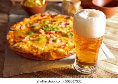 Glass of fresh beer and tasty pizza on background