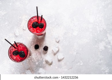 Glass with Fresh Blackberry Lemonade Beverage. Frozen Refreshing Mixed Blueberry with Water Cocktail and Ice Cubes in Goblet. Homemade Organic Natural Drink with Tubules on Light Background Flat Lay