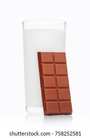 Glass of fresh breakfast milk with chocolate bar on white background