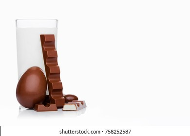 Glass of fresh breakfast milk with chocolate bar egg and candies on white background