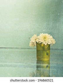 Glass fresh chamomile flowers is on reflection table and blue wall background