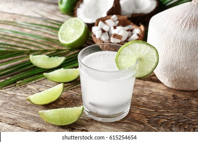 Glass of fresh coconut milk with lime on wooden table