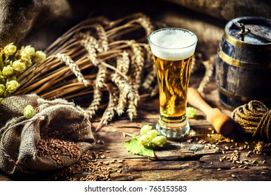 Glass of fresh cold beer in rustic setting. Food and beverage background