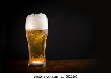 Glass of fresh cold chilled beer with black background