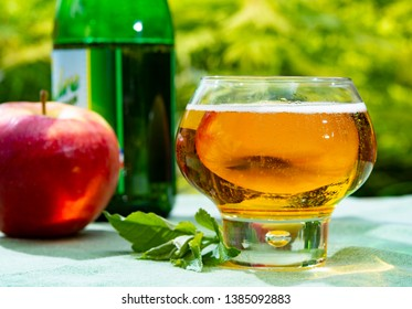 Glass with fresh cold French apple cider drink from Normandy region served with apples in green garden