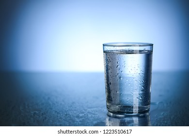 Glass of fresh cool water on table