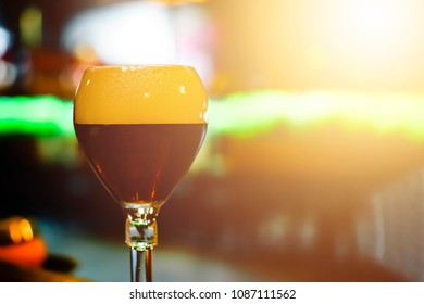 Glass of fresh dark beer on rustic pub background. The Belgian-style dubbel ranges from brown to very dark in color. They have a malty sweetness , cocoa and caramel aromas and flavors.