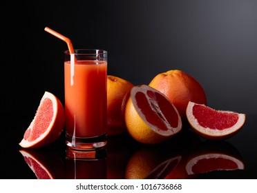 Glass of fresh grapefruit juice and cut fruits on black background.