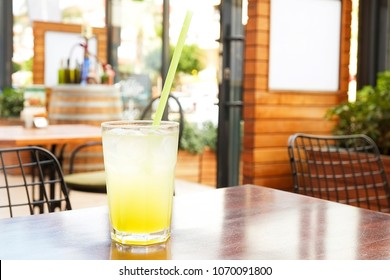A glass of fresh ice cold lemonade on wooden table of coffee shop patio with green bushes on background. Close up of refreshing lemon juice cold beverage on the cafe terrace, outside. Text copy space