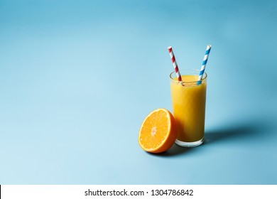 a glass of fresh juce and two paper tubes next to a lemon and an orange on a blue background with copy space