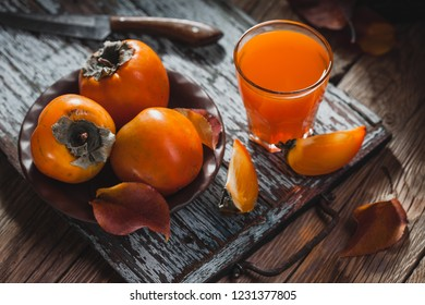 a glass of fresh juice and ripe orange persimmon fruit and persimmon leaves in a brown plate on a brown wooden table. fresh fruits
