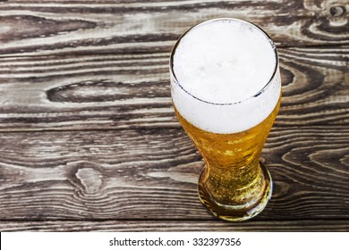 glass of fresh lager beer on a wooden table. focus on Foam