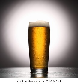 glass of fresh lager beer on light studio background with reflection