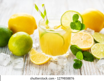 Glass with fresh lemon juice on a old wooden table