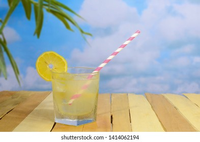 A glass of fresh lemonade on ice with a lemon garnish and a fun red and white barber pole style straw on a rustic wooden table that is outdoors with palm leaves and a partly cloudy blue sky