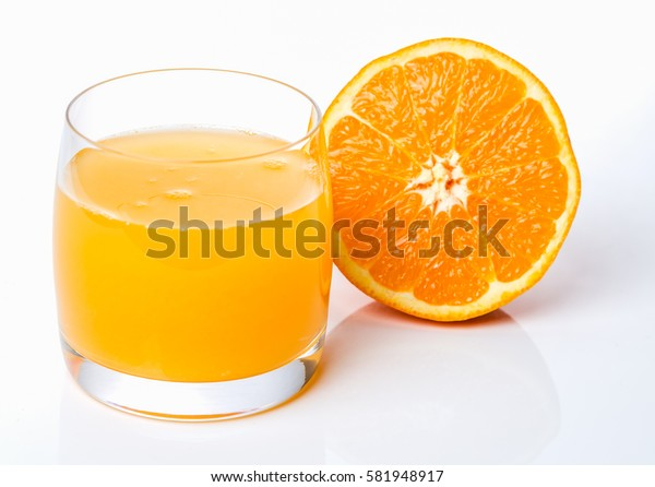 Glass of fresh made orange juice with an half orange slightly in the background on white