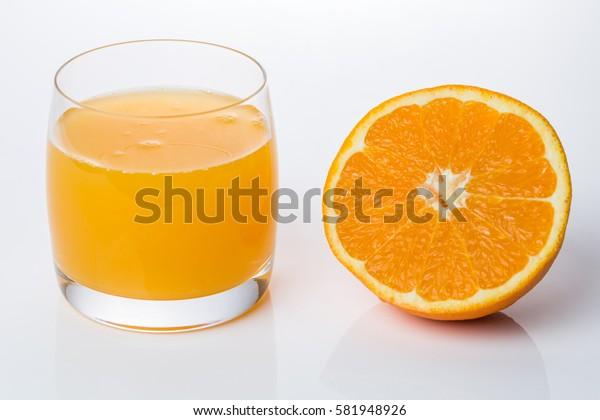 Glass of fresh made orange juice with an half orange aside on white background