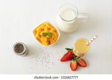 Glass of fresh mango smoothie or mango milkshake with milk in glass pitcher, chia seeds, pieces of mango in porcelain bowl and few real fresh strawberries on white wooden table. Top view.