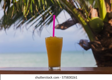glass of fresh mango with a straw under a palm tree on sea background
