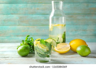 Glass of fresh mojito with lime and lemon on light wooden table