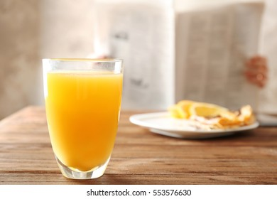 Glass of fresh orange juice and breakfast on table